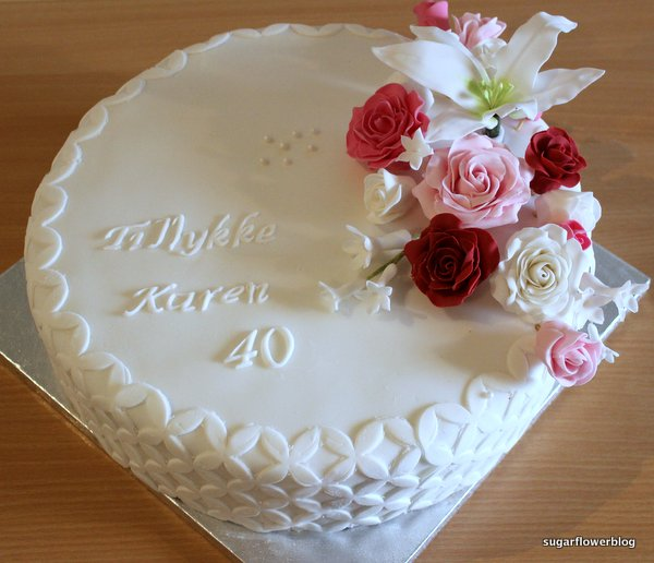 Birthday cake with roses lily and stephanotis flowers Karens